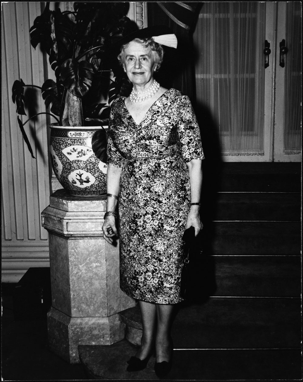 Woman in a dress, standing in front of a stair case.