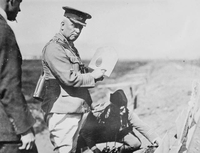 Black-and-white photograph showing three men, two are clearly in uniform. One officer (Minister of Militia Sam Hughes) is holding the MacAdam shield-shovel which is a spade-shaped piece of metal with a hole on one side, while the other officer is kneeling on the ground doing something indiscernible. The third is looking at the spade.