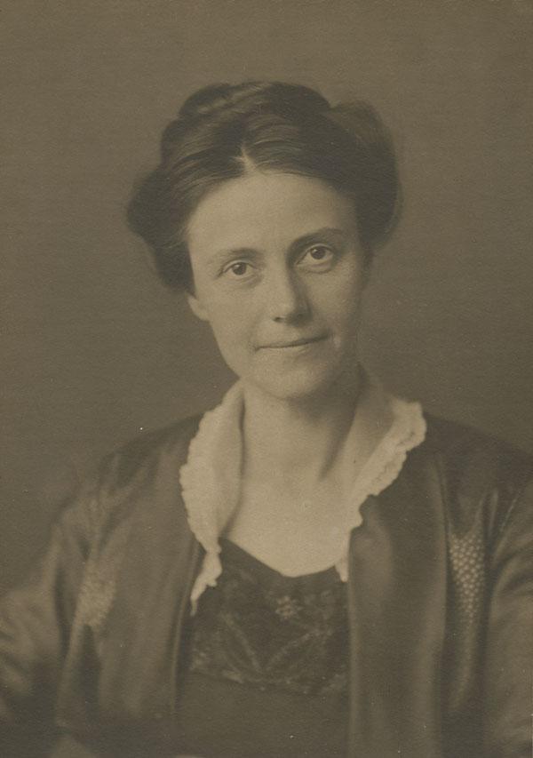 Photographie en plan-serré, noir et blanc, d'une femme avec un petit sourire.