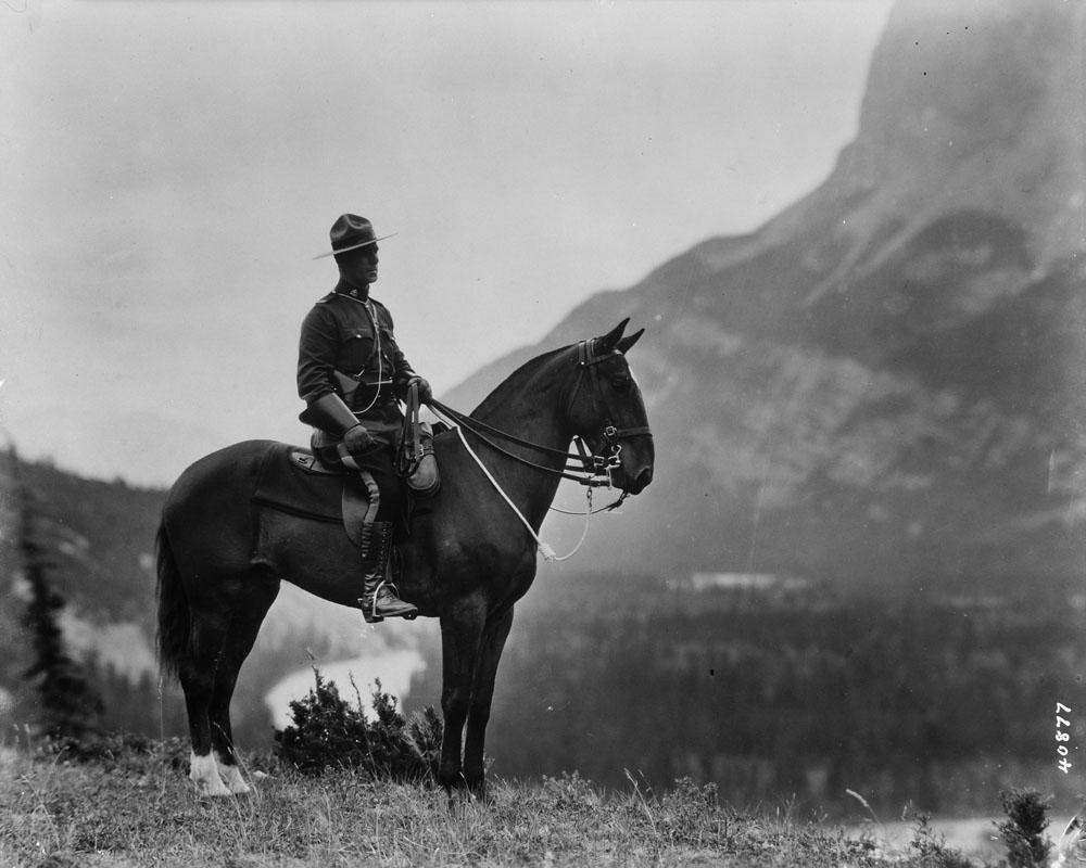 Photo en noir et blanc d'un officier à cheval, en uniforme et coiffé d'un Stetson de style western, avec les Rocheuses canadiennes à l'arrière-plan.
