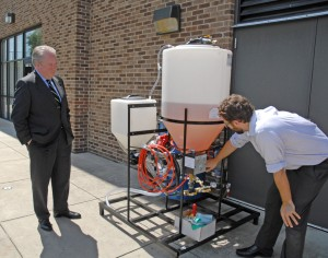 Dr. Danny Monroe (right), head of the VGCC Bioprocess Technology program, describes how his program's biodiesel production equipment works to U.S. Rep. George Holding (left) during the congressman's campus tour. (VGCC photo)