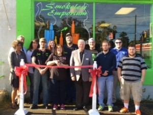 Shown at the Henderson-Vance Chamber of Commerce ribbon cutting for Smokeless Emporium are, (front row) Vanessa Jones, HVCC Work First Coordinator; Josh Gilley and Julie Moore, Smokeless Emporium; Mayor Pete O'Geary; Tyler White; Matthew Hatchel; (back row) John Barnes, HVCC President; Heather Tuck; Megan Lee; Brian and Daniel Moore, Smokeless Emporium; Chamber Ambassador Kevin Bullock, WIZS 1450.. Not Pictured: Melanie Mann, HVCC Office Manager