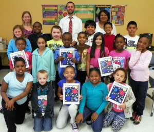 The students are shown  holding copies of their book and are joined by, on the back row from left, Ireland, Assistant Principal Patrick Sutton and Principal Crystal Richardson, in their classroom at Clarke Elementary.