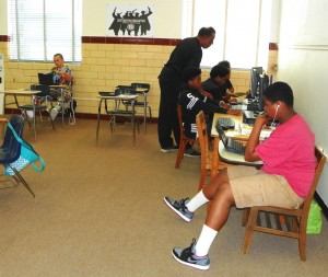 Pictured are Reginald Moore, a teacher at Henderson Middle School, assisting a student with online instruction at the Youth Empowerment Academy.