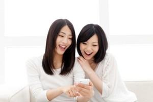 携帯電話を見て笑う女性2人
