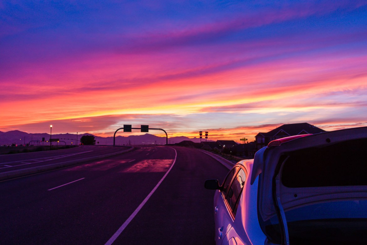 My car parked on the road under a beautiful sunset