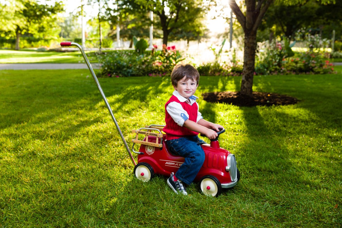 Sunrise and Alexander rides his Radio Flyer Fire Truck in the grass