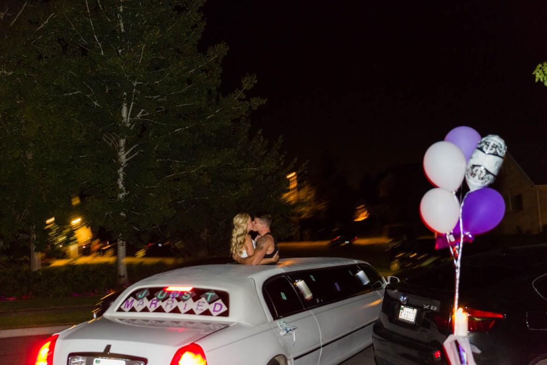 Wedding couple kiss as limo departs