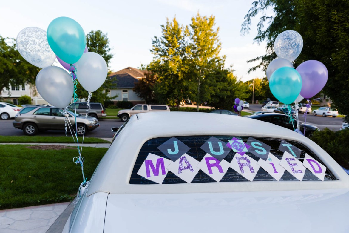 Wedding limo is decorated with balloons and just married sign