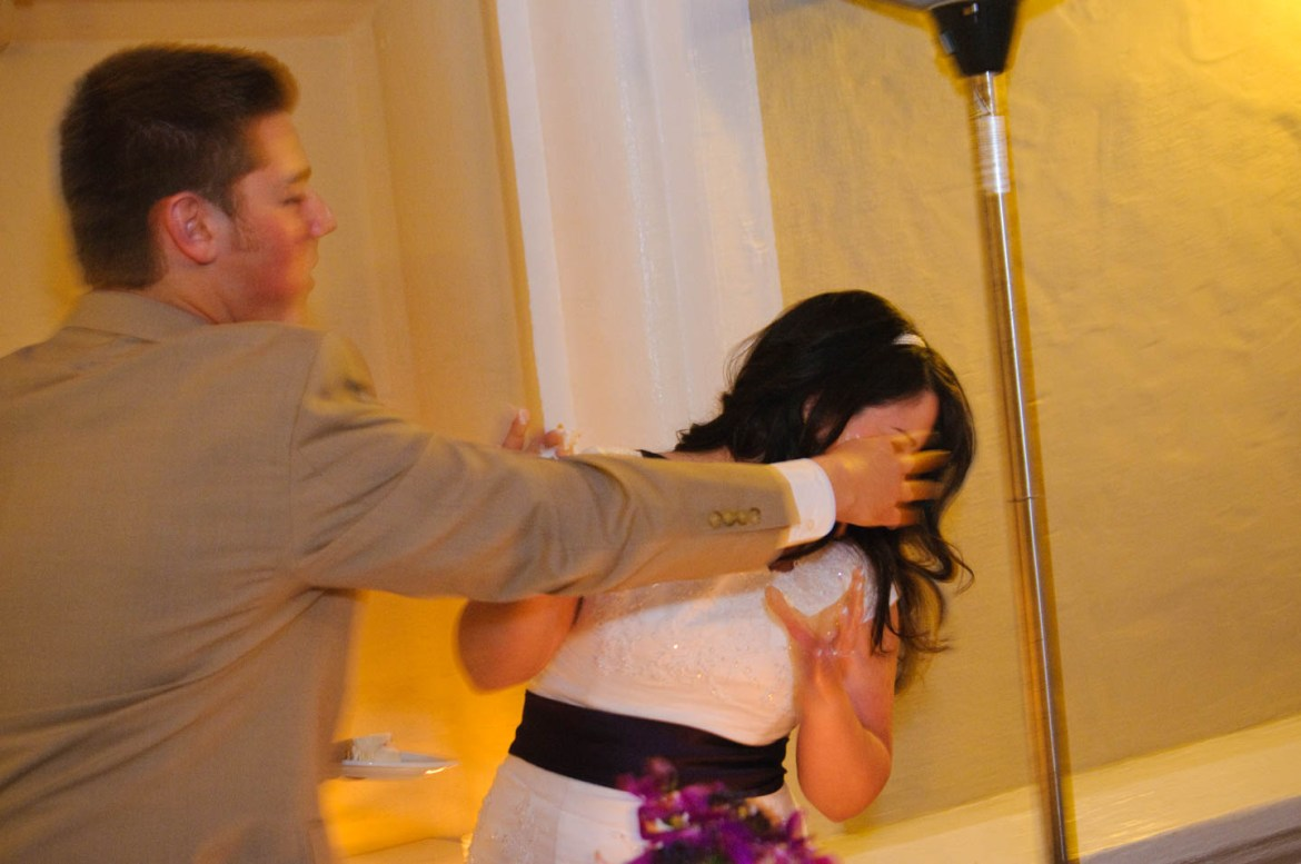 Groom smashes cake on the bride