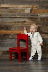 Little Arthur waves while standing by the red chair