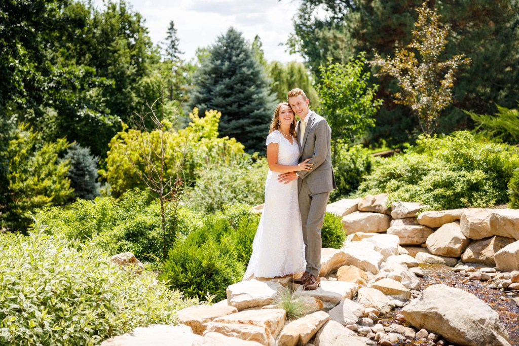 Couple stand on rocks for wedding portrait