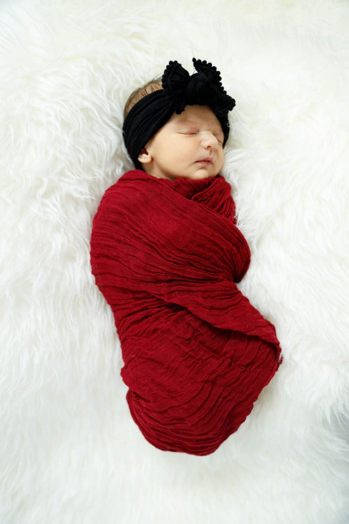 Baby Nora bundled in red on white fur