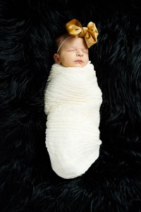 Baby Nora bundled on black fur