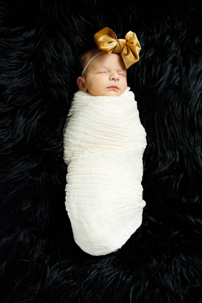 Baby Nora bundled on black fur