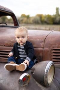 Baby boy sitting on an antique truck