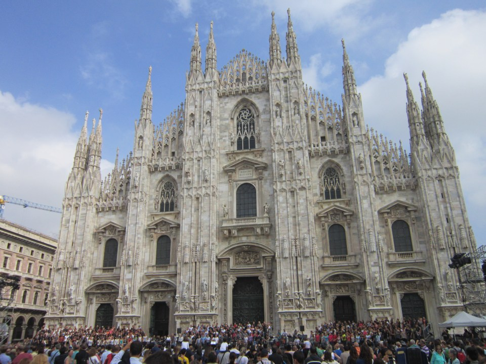The outside of the Duomo in Milan. Italy backpacking itinerary. Showing the front of the cathedral with many people outside of it.