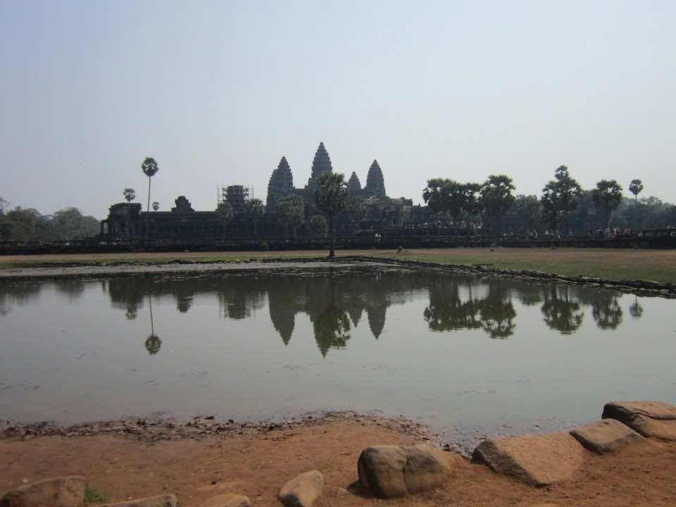 View across water of Angkor Wat in Cambodia. Backpacking tips - go see the big sights!