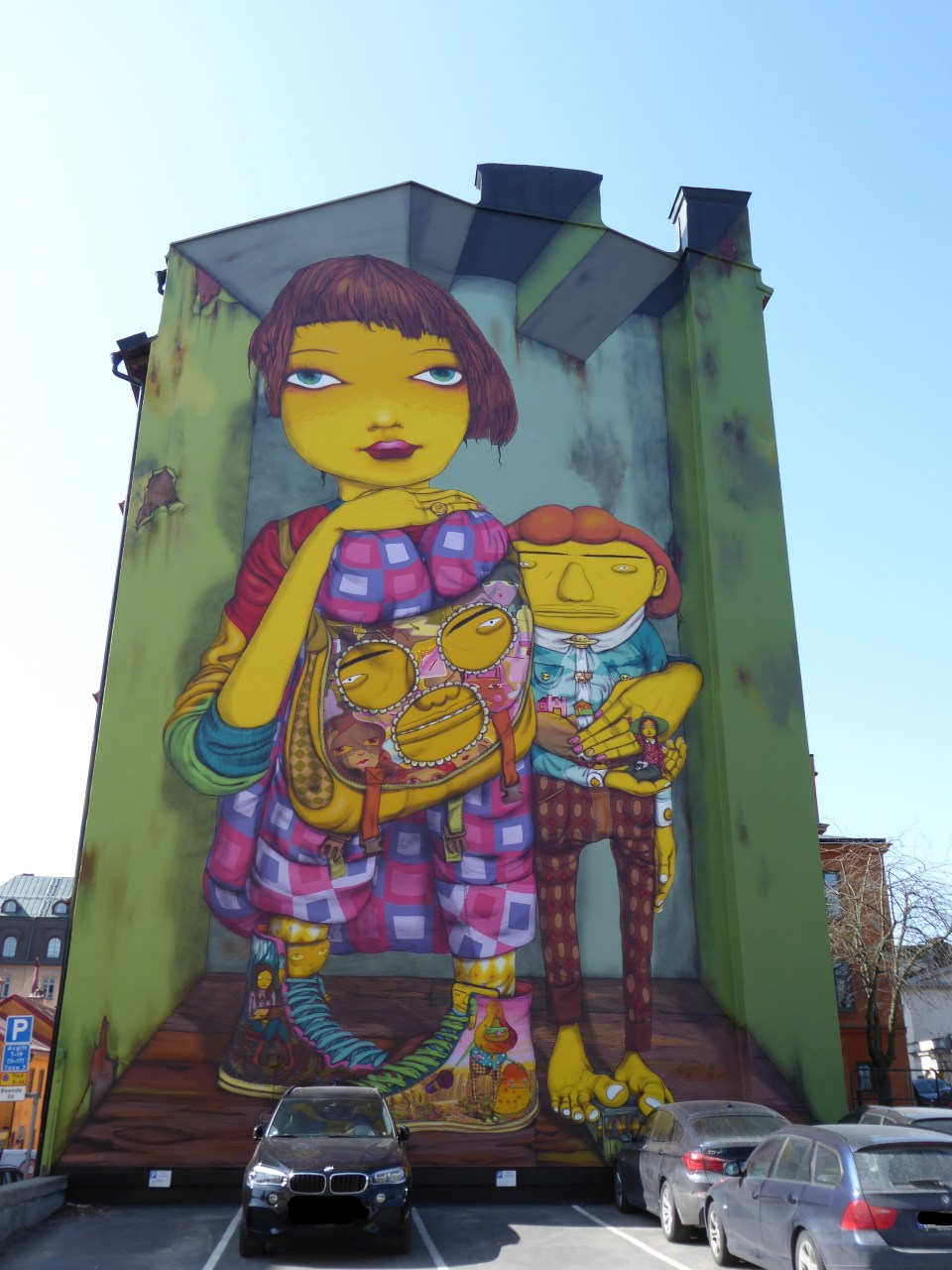 Mural in Södermalm, Stockholm. Featuring people with yellow skin and a green background. On a large building side, with cars parked in front.