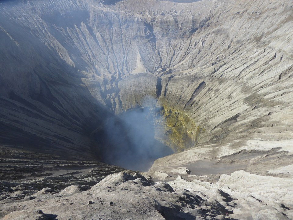 Looking down into the Mount Bromo crater. There is a touch of smoke rising from inside.