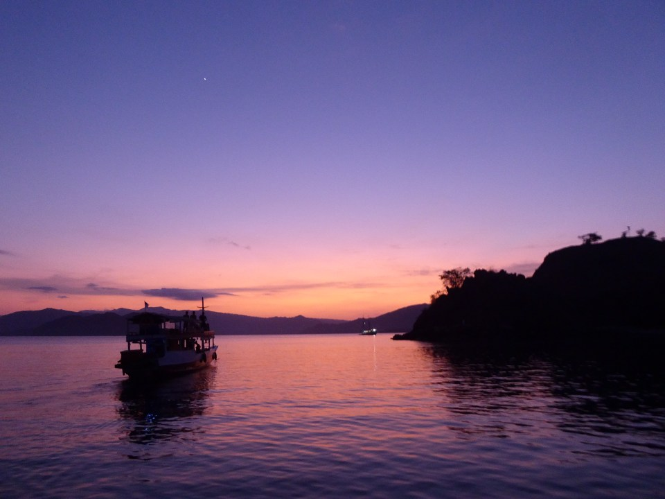 Komodo Islands Travel Guide - Sunrise in the Komodo National park - showing a boat and purplish sky