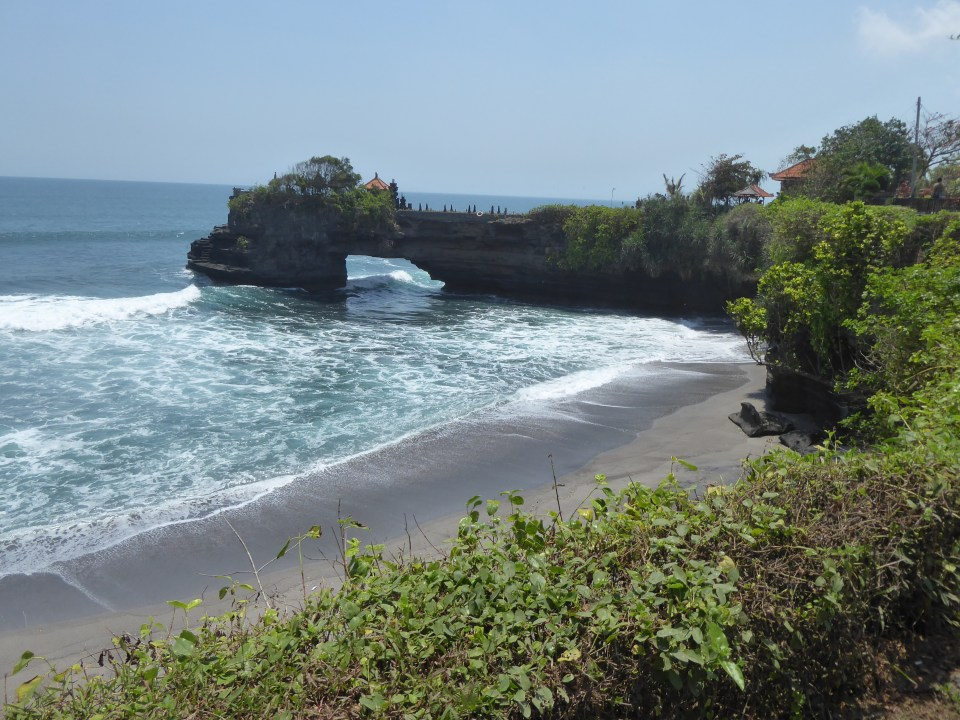 Looking towards the sea arch with Batu Bolong on its end. In the Tanah Lot temple complex