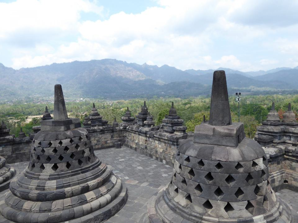 Looking out from the top of Borobudur, past multiple stupa's towards mountains.