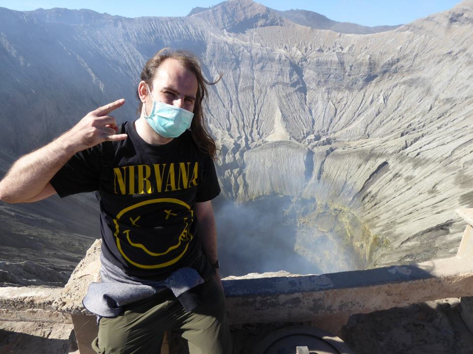 Dave from Dave Does The Travel Thing at the top of Mount Bromo, with smoke rising from the crater behind him.
