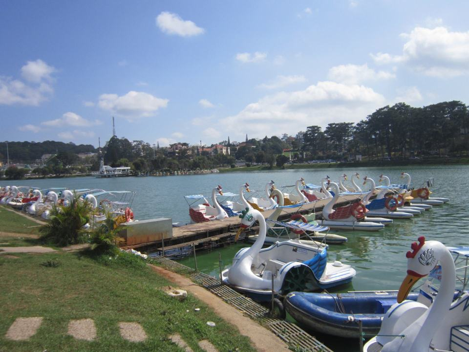 Swan boats on the lake in da Lat on a sunny day, with a few cloud sin the sky