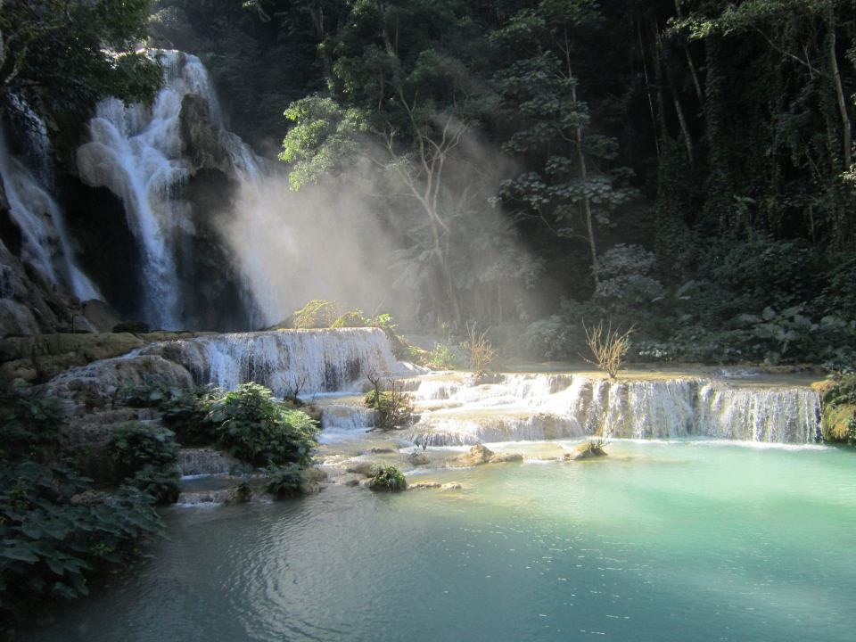 Kuang Si waterfalls. Mist rises above a pool with a waterfall in the background. One of the most scenic places you can visit on this list of cities in Southeast Asia.