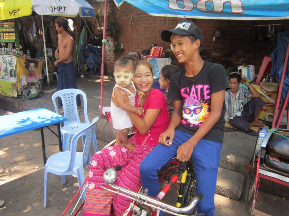 A female and male with their baby pose for photos in Yangon. Its one of the best cities in Southeast Asia to interact with local people.