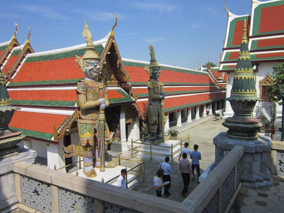 2 giant Buddhist statues guarding an entrance to a building at the Grand palace. A recommend first stop on this list of Southeast Asian temples.