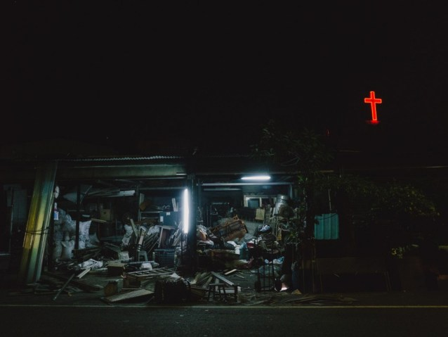 A neon cross in the distance above a wood salvager