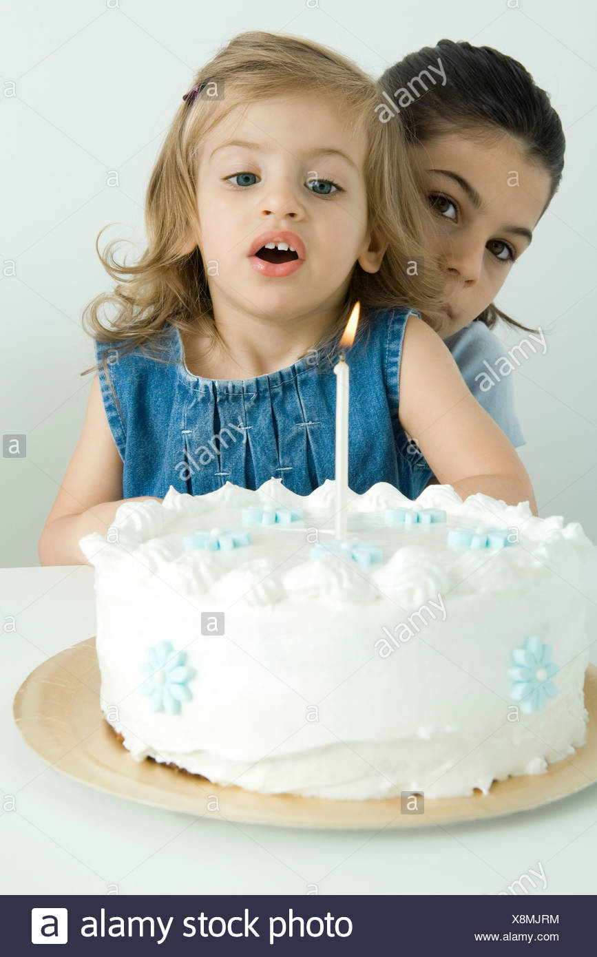 Birthday Cake For Sister Girl Blowing Out Candle On Birthday Cake Sister Peeking At Camera
