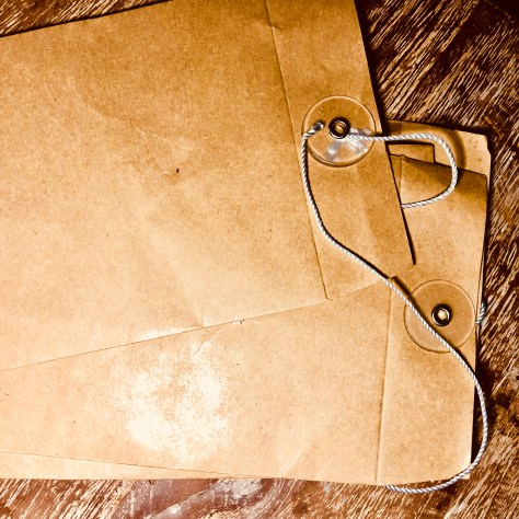 Items: stationery, envelopes (manila, bank-sized, with string closure)