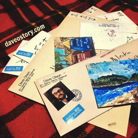 A stack of decorated envelopes with airmail stickers, return address stamp plus 1 yen postal stamps of teddy bears, ink stamps of anchor and shiba-inu dog along with postcards oil paintings of a beach scene and an acrylic painting of postboxes in Nepal along with a picture of the creator, Dave Olson in a headband. All atop a plaid wool blanket.