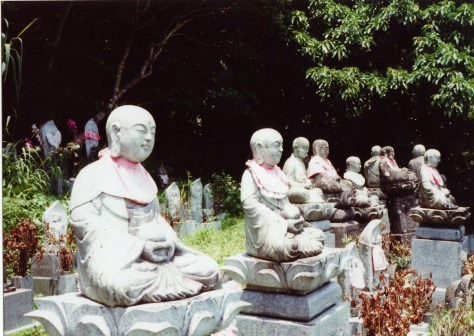 Japan hitch-hiking: constantly pleased by the decorative outfits on the Buddha statue/grave markers - besides bibs, often knit hat and snacks like oranges, crackers and sometimes small boxes of sake