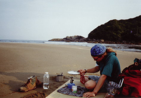Japan hitch-hiking: beach camping on Shikoku, in this moment, preparing pop-corn on a button camp stove (actual tent location at higher ground due to tides)