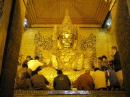 Mahamuni Pagoda. Gold leaf continues to be applied distorting the original Buddha image.