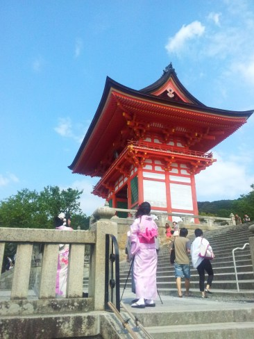 A woman in a kimono in front of a shrine at Kiyomizu-dera temple in Kyoto.