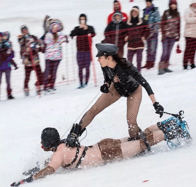 Picture of a dominatrix riding her half-naked sub down a snowy hill like a sled