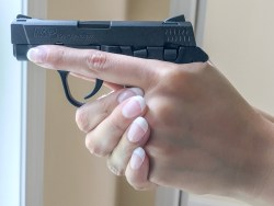 Firing side view of two-handed grip on small pistol by large left-handed shooter