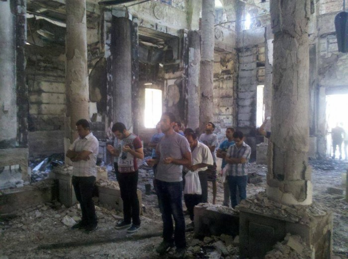 Copts pray in the burnt husk of a church