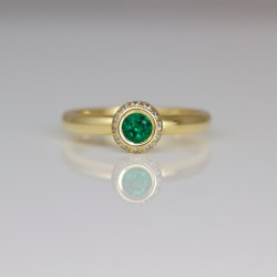 modern emerald ring with diamond halo