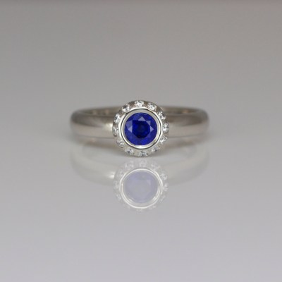 Blue sapphire with diamond halo platinum ring