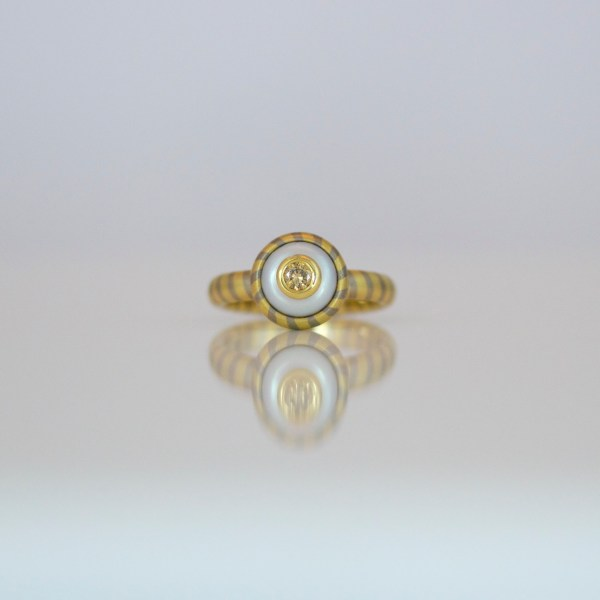Natural yellow diamond set in a pearl, contemporary diagonal stripe ring