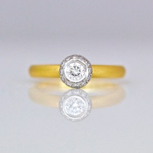 18ct yellow gold rub-over set diamond halo ring.