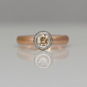Natural pink champagne diamond rub-over set in platinum with white diamonds halo on rose gold ring