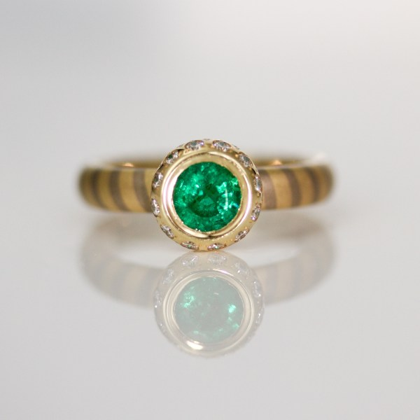 Emerald with diamond halo on diagonal stripe ring