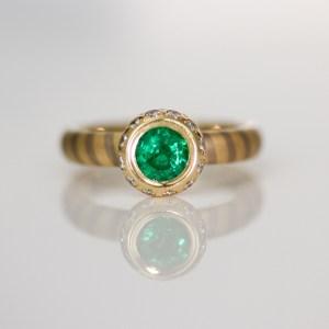 Emerald with diamond halo on diagonal stripe ring
